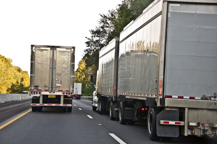A Convoy of 18-wheelers rolling on down the highway.