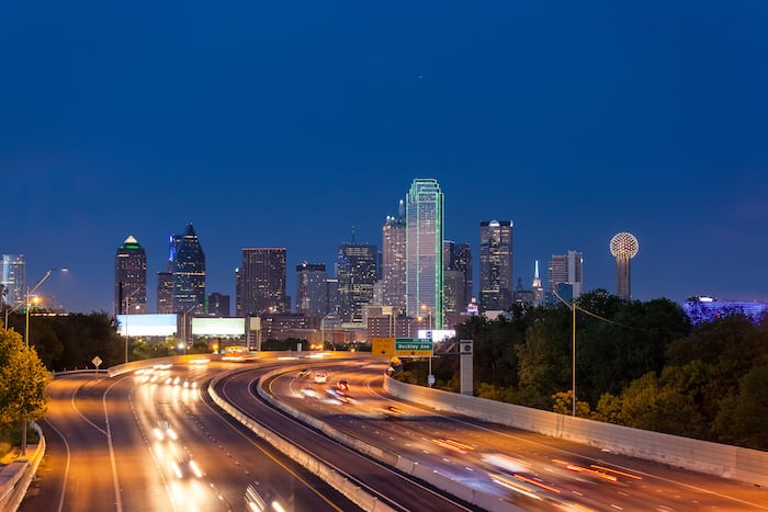 A freeway leads to the Dallas downtown skyline at night, Texas