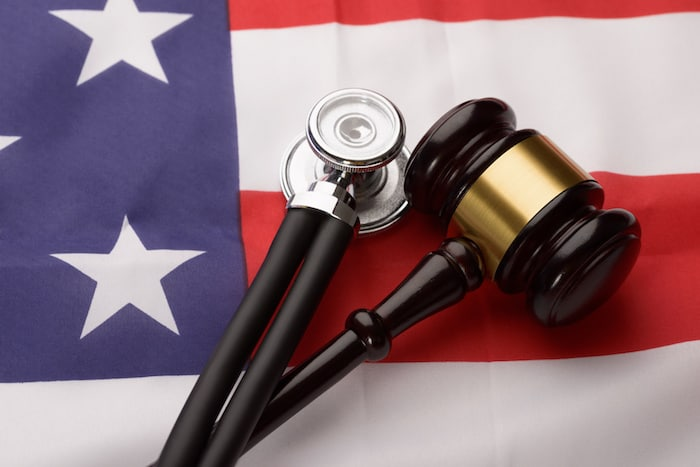 Close-up Of Wooden Brown Gavel And Stethoscope On Usa Flag