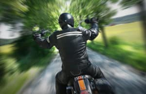 A motorcycle rider speeds down a country road