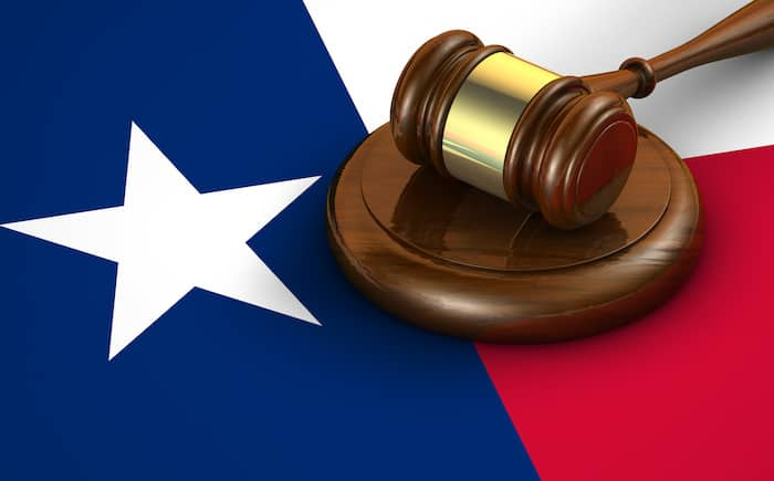 Texas us state law, code, legal system and justice concept with a 3d render of a gavel on the Texan flag on background.