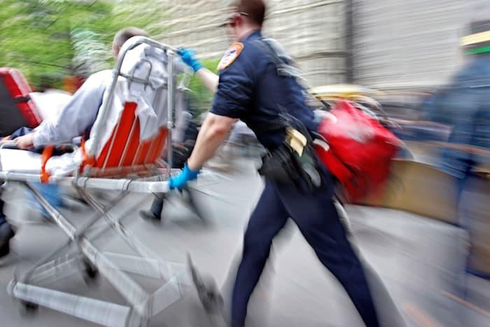 Paramedics wheel a victim to an ambulance after an accident