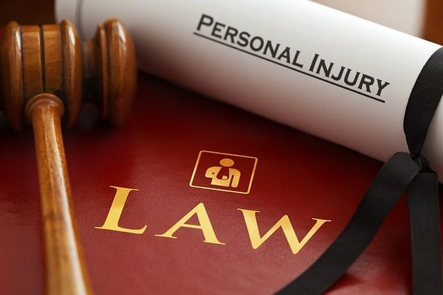 A gavel and Personal injury scroll sit atop a law book