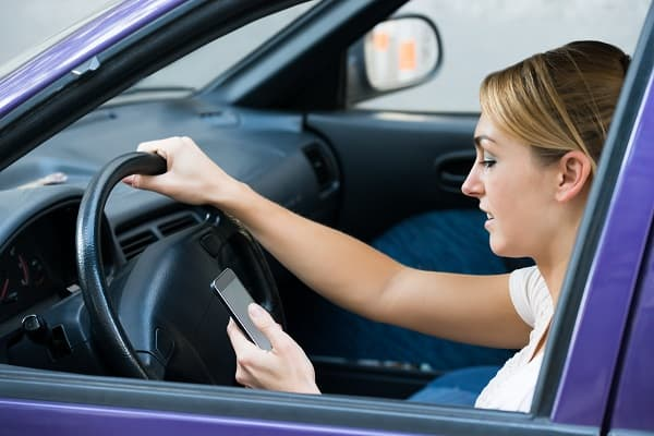 Young woman using cell phone while driving car
