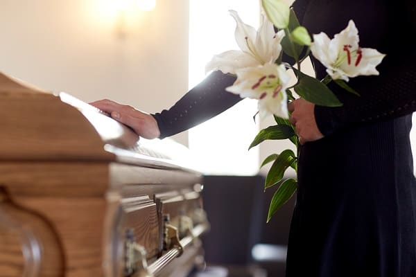 A woman with white lily flowers and coffin at funeral in church