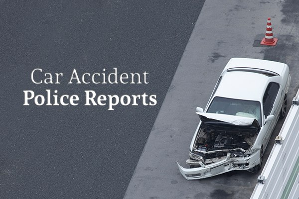 "A white car that has been in a car accident sits on the highway shoulder beside the words ""Car Accident Police Reports"""