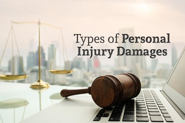 "A gavel sits on a laptop with scales in front of scales with a city skyline in the background and the words ""Types of Personal Injury Damages"