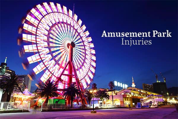 "An amusement park with a Ferris Wheel showing predominantly beside the words ""Amusement Park Injuries"""