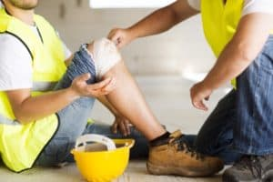 A construction worker is getting his knee bandaged after an accident.