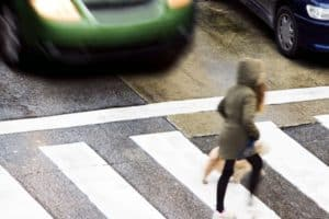 A lady and her dog are crossing a crosswalk on a dangerous street.