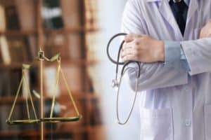 A doctor standing next to a pair of legal scales and holding a stethoscope.