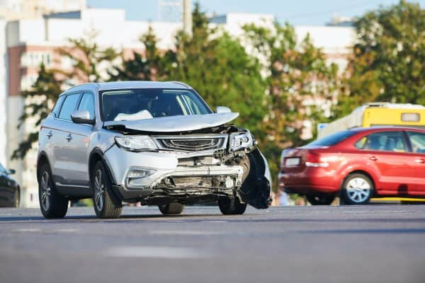 A car accident involving a silver SUV with a smashed in hood.