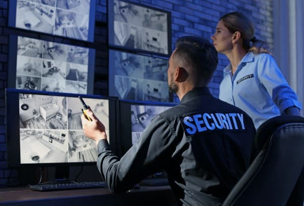 A security guard looking over monitors.