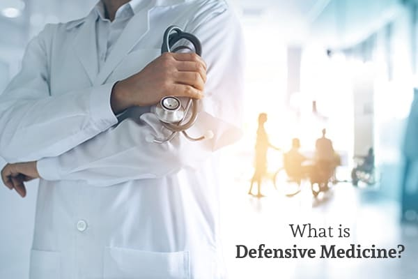 A doctor has his arms crossed with patients in the background along with the words, what is defensive medicine.