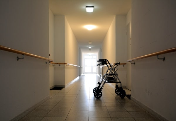 A walker alone in the middle of a hallway.