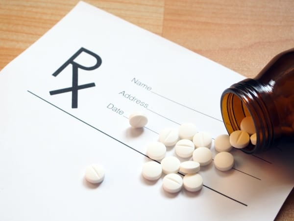 A prescription with an open bottle of pills overtop of it.